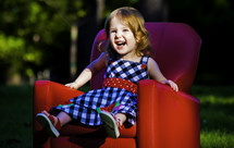 child sitting in a red chair outdoors