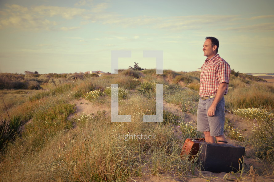 a man with luggage standing alone on sand dunes