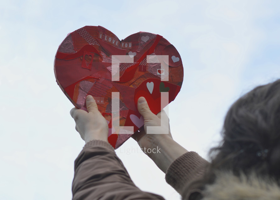 woman holding up a paper heart heavenwards