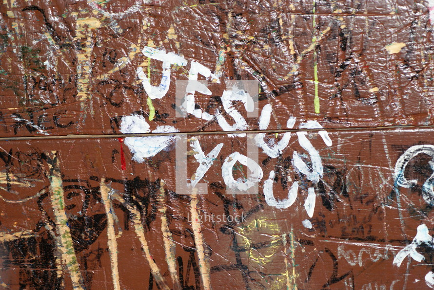 """""""Jesus loves you"""" written on a wall covered in graffiti."""