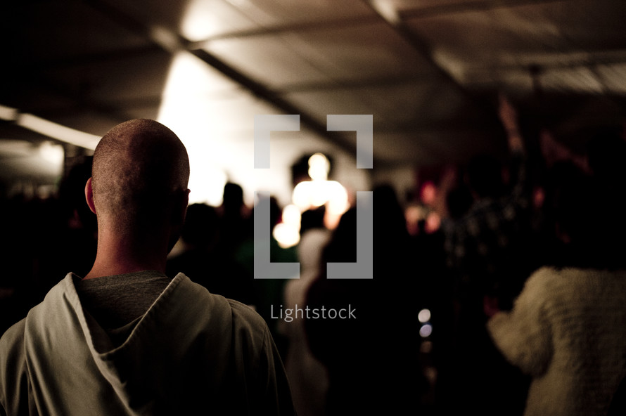 Audience facing an illuminated speaker on stage.