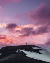 a man standing on a mountaintop under a purple sky with hands raised