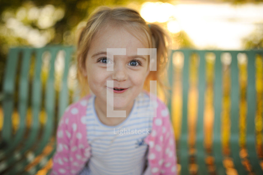 a little girl on a bench outdoors