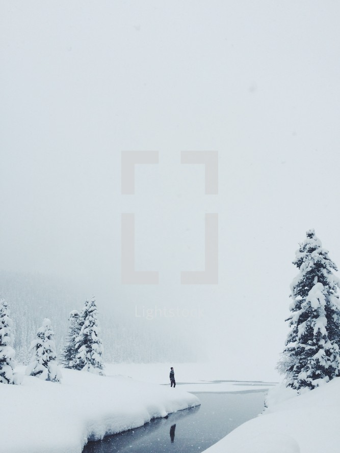a man standing on the riverbank of a winter river