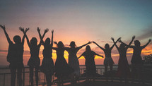 silhouettes of women with hands raised