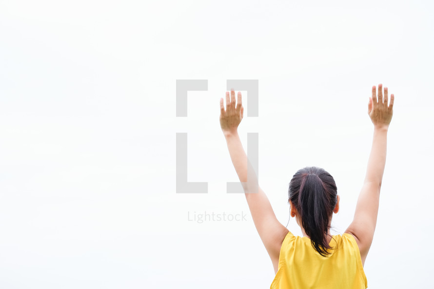 young woman with arms raised