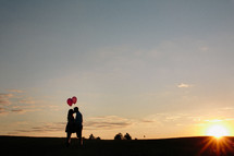 man and woman in an embrace holding balloons