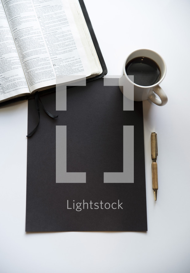opened Bible, coffee, blank black paper, and pen