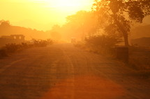 glow of the sun at sunset over a dirt road