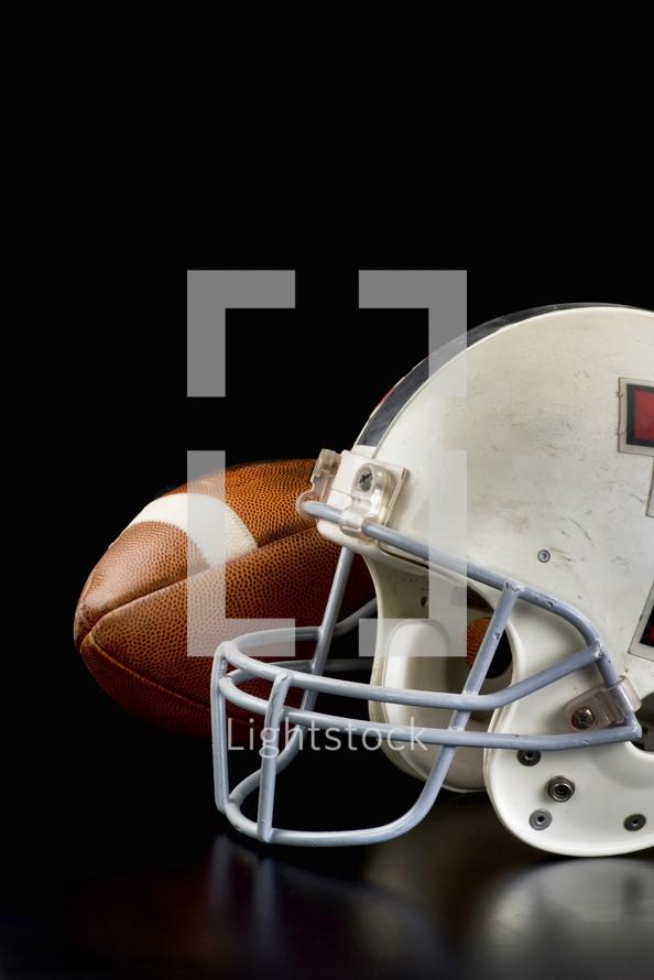 football and football helmet on a black background