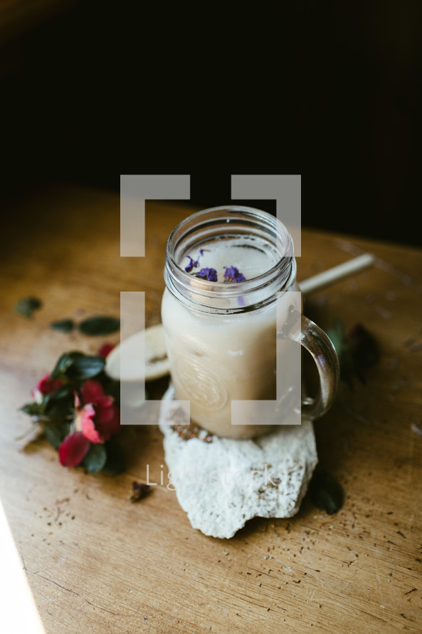 flowers, wooden spoon, glass mug, and rock