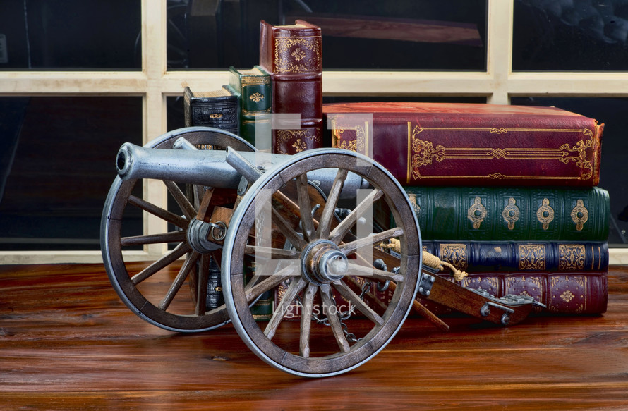 cannon decoration and books on a table