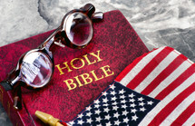 spectacles, Holy Bible, and American flag
