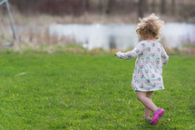 toddler girl running in grass