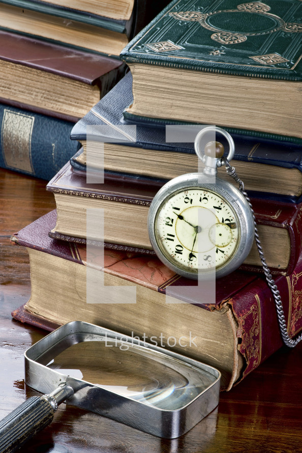 pocket watch, magnifying glass, and stacked books on a desk