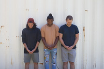 men standing together with heads bowed in prayer