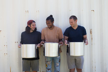 volunteers holding pots of soup at a soup kitchen
