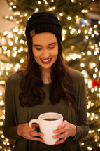 a woman holding hot cocoa in front of Christmas tree