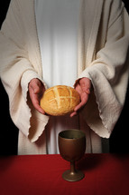 Priest hold a loaf of bread with a goblet of wine on the table