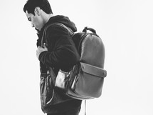 young man with a leather backpack