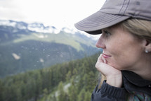 side profile of a woman in a ball cap looking out at mountains