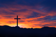 Silhouette of a cross on a hill under a red sky.