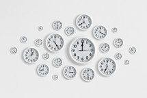 Round white clocks on a white wall.