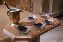Bowls of ashes and holy water on a table, preparing for Ash Wednesday.