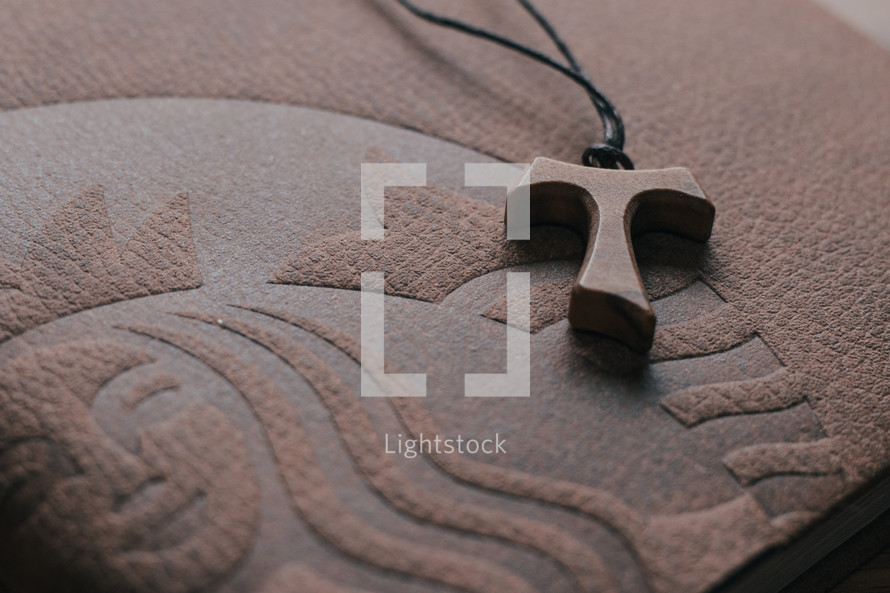 tau cross necklace on a Bible