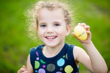 a little girl holding an Easter egg