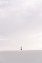 a man standing at the top of a sand dune