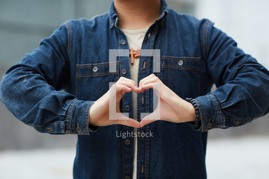 young man creating a heart symbol with his hands