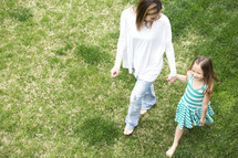 a mother and daughter walking holding hands through grass