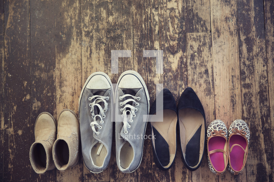 family shoes on an old wooden floor.