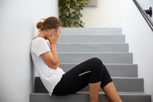 a stressed woman sitting on steps outdoors