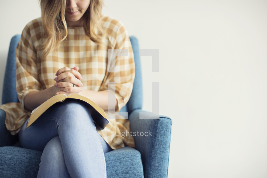 a woman sitting in a chair praying over an open Bible