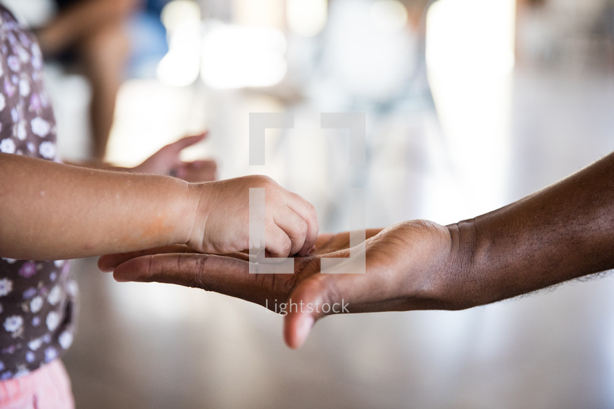 a child's hand touching an adult's hand