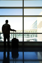 A man with luggage starring out an airport window