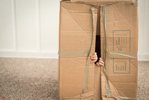 child playing with a cardboard box