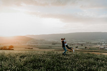 couple embracing on a hill at sunset