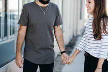 couple on a sidewalk holding hands