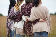 group of young women in a field with arms around each other
