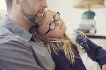 A little girl in glasses sits in her father's lap and looks at his face.