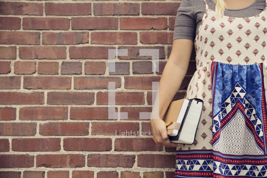 student holding a Bible and journal at her side against a brick wall.