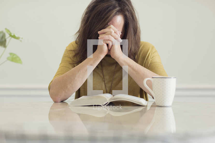 a woman praying over a Bible sitting at a kitchen table