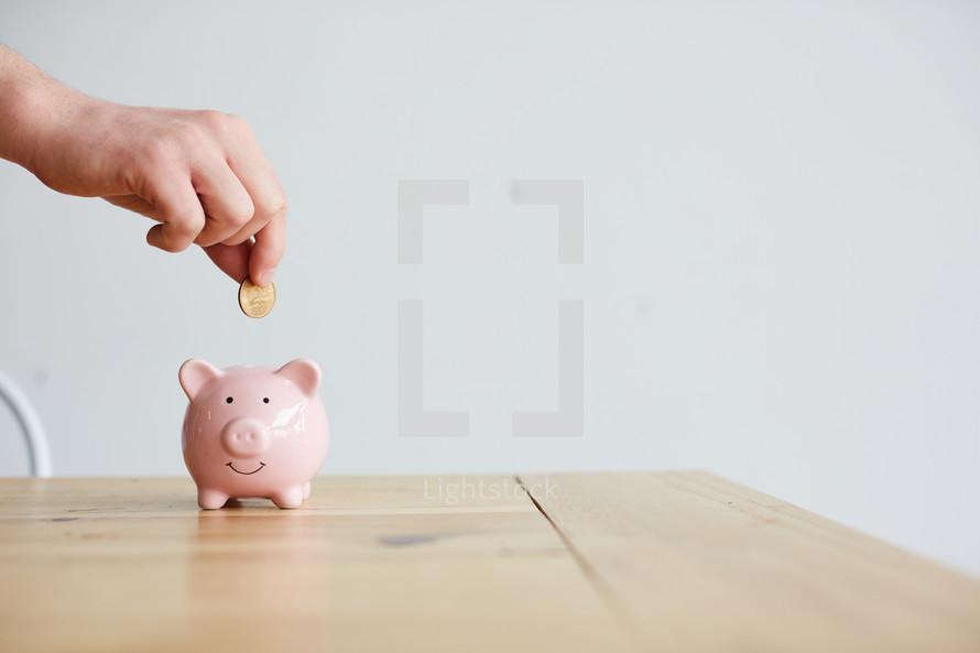 man putting coins into a piggy bank