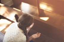 a woman praying in church pews