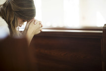 a woman with her head bowed in prayer over a pew