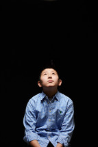 a boy child looking up to God