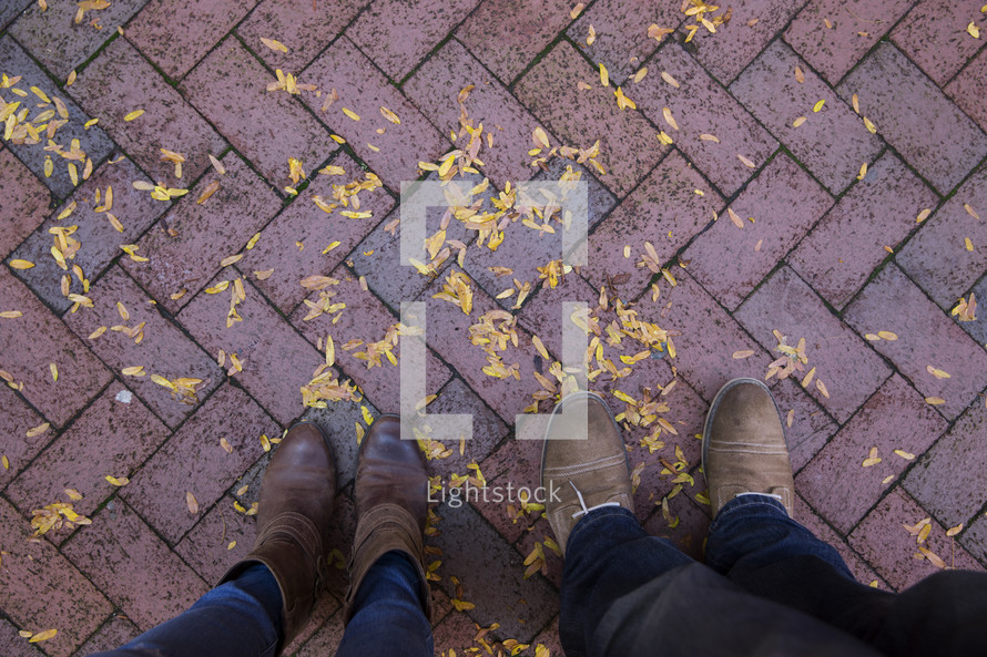 man and a woman standing on a brick patio